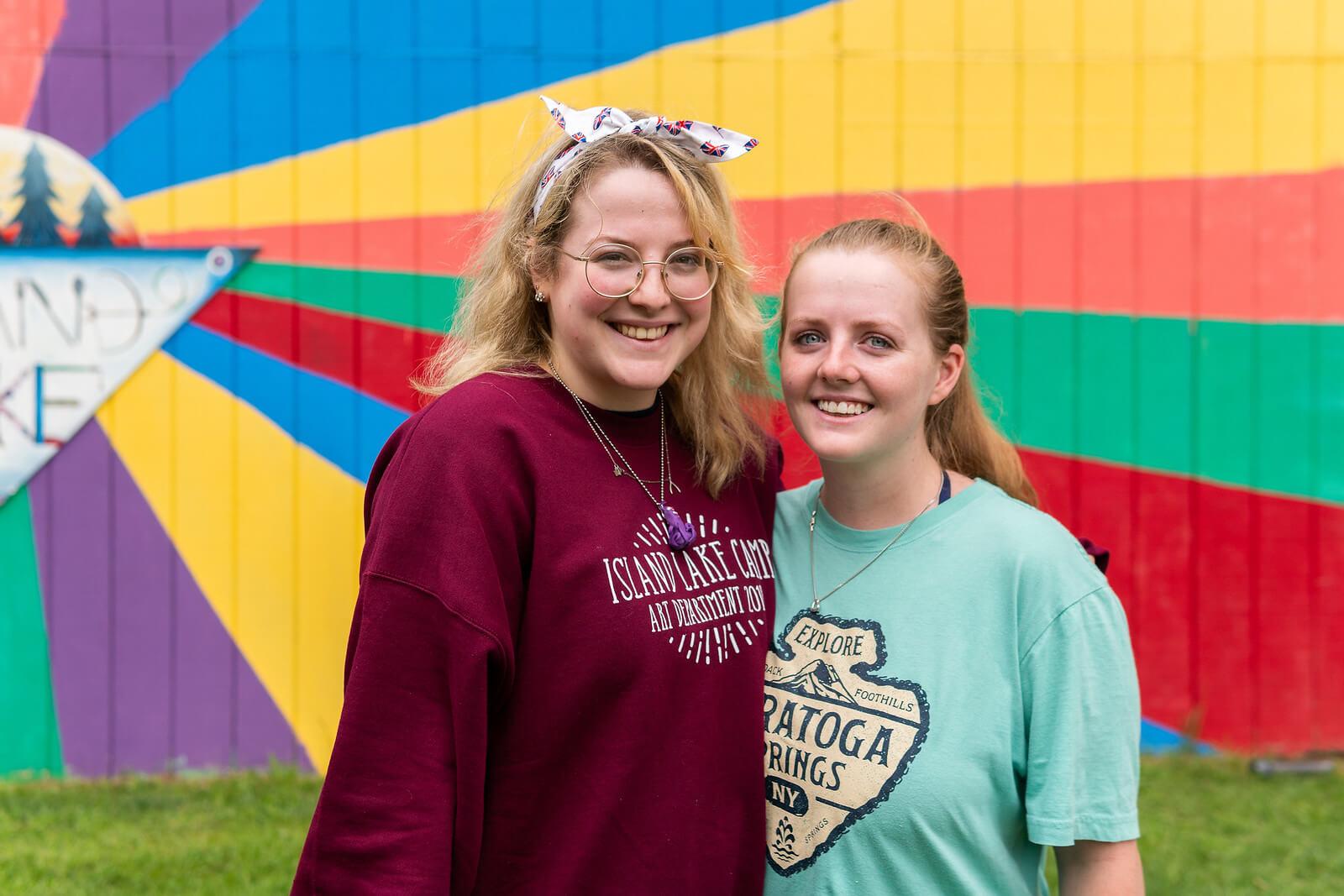 Dwie przytulone dziewczyny pracujące na campie Island Lake Camp w USA