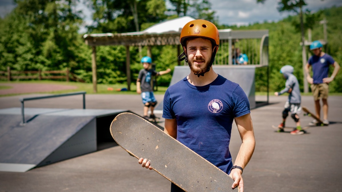 male skateboard counselor working at summer camp